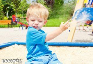 Foto van kindje dat gooit met zand-Goodwill.nl