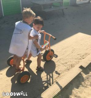 2 kinderen van Youké spelen met de nieuwe driewieler van Goodwill