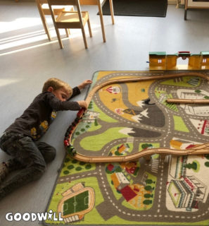 Liggend op de grond met de trein spelen-Goodwill.nl