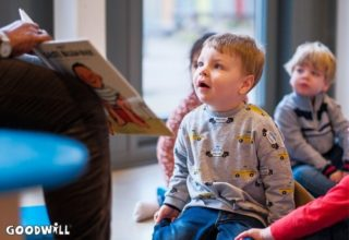 Een kindje kijkt met grote ogen naar Gerda Havertong die een boek voorleest-Goodwill.nl