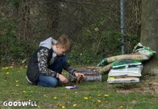 Foto van een jongen bij zakken aarde en mest voor de moestuin-Goodwill.nl